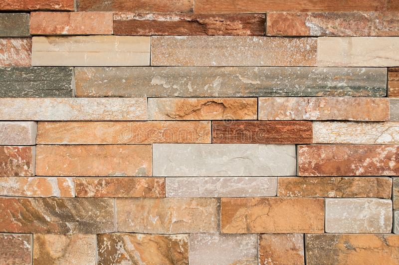 Grunge brown stone wall tiles texture. Wall natural brown,orange stone dirty,dust with pattern design or abstract background royalty free stock photos
