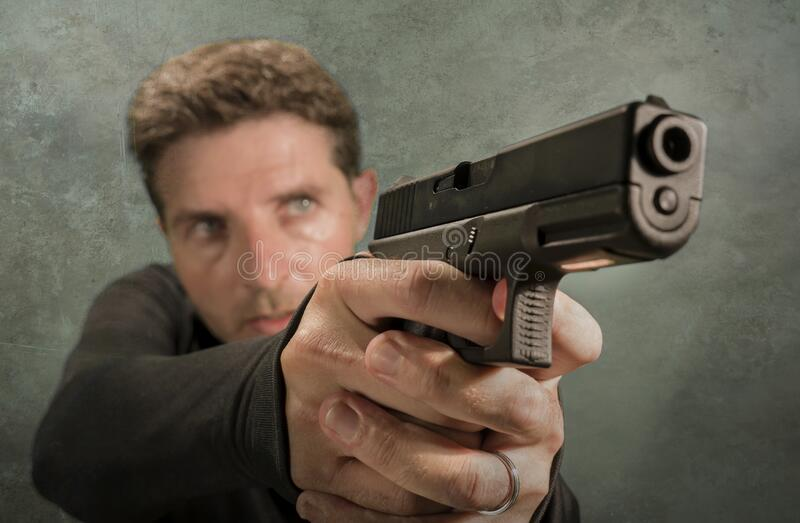 Grunge cinematic portrait of attractive and dangerous looking hitman or secret service especial agent man in action pointing gun stock images