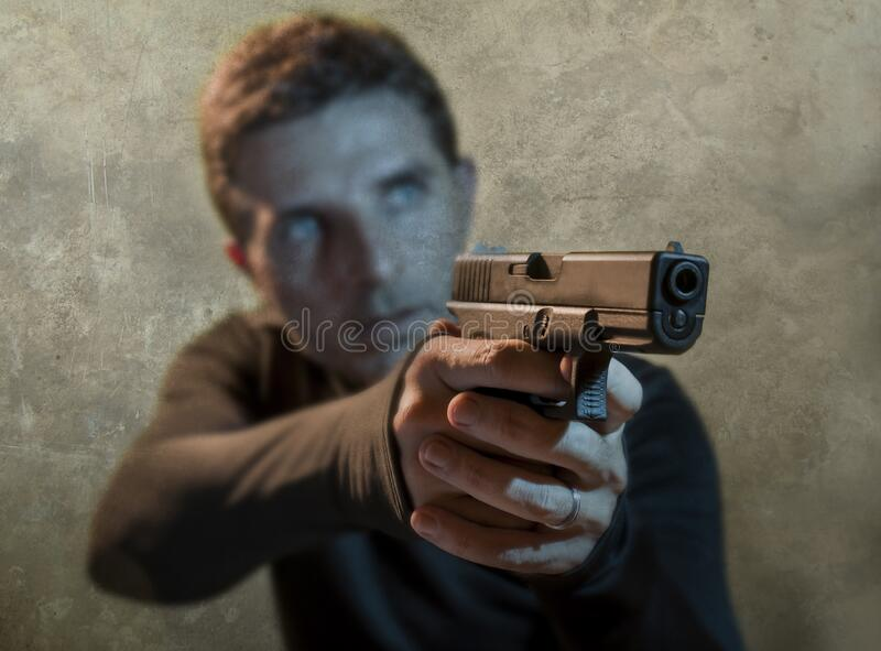 Grunge cinematic portrait of attractive and dangerous looking hitman or secret service especial agent man in action pointing gun stock photography