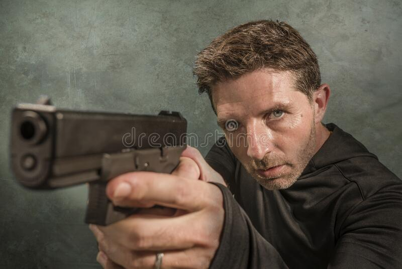Grunge cinematic portrait of attractive and dangerous looking hitman or secret service especial agent man in action pointing gun royalty free stock photo