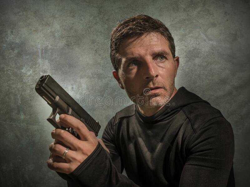 Grunge cinematic portrait of attractive and dangerous looking hitman or secret service especial agent man in action pointing gun royalty free stock photography