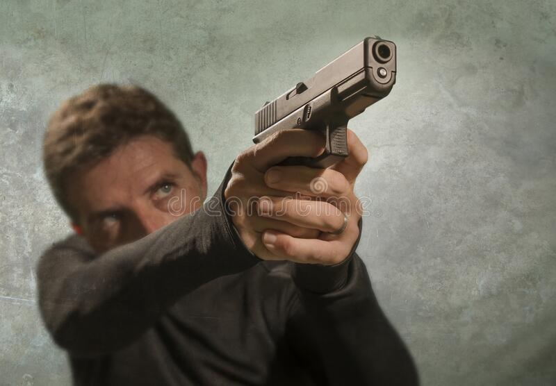 Grunge cinematic portrait of attractive and dangerous looking hitman or secret service especial agent man in action pointing gun stock image