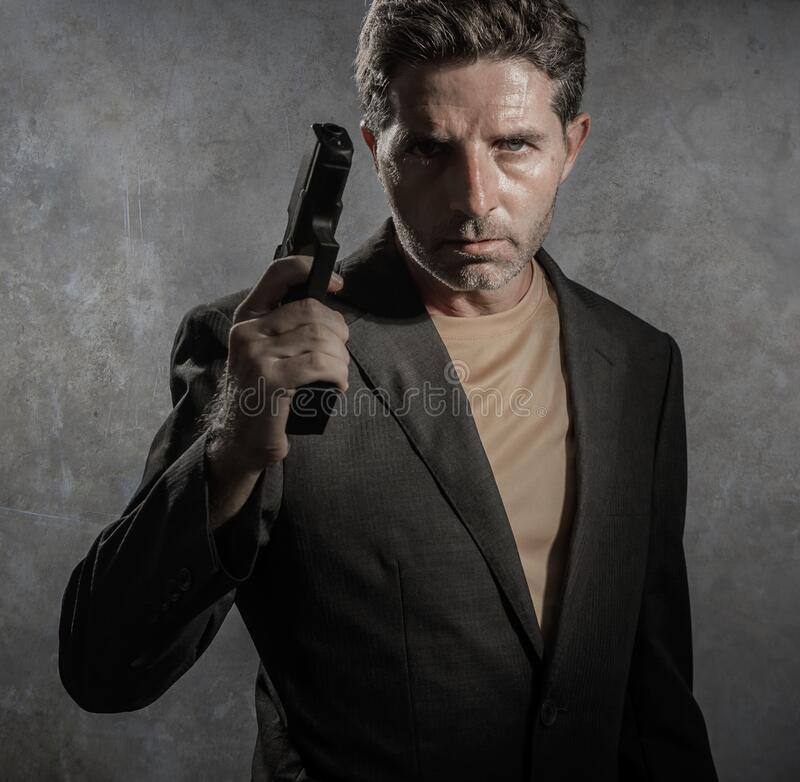 Grunge cinematic portrait of attractive and dangerous looking mafia hitman or secret service especial agent man in blazer pointing royalty free stock photography
