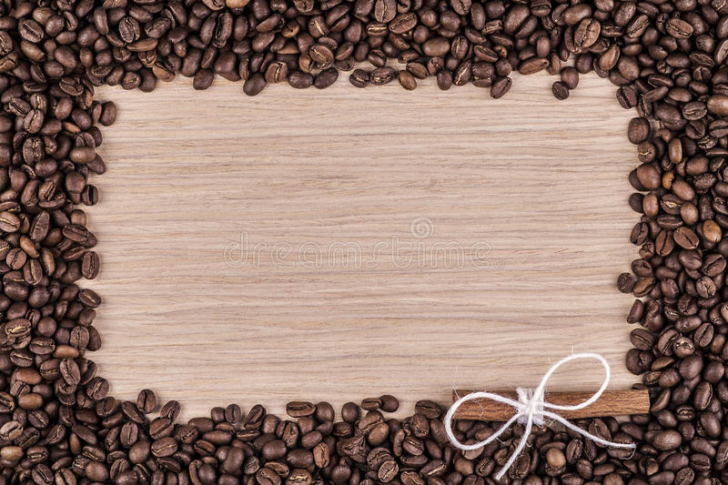 Grunge coffee frame. Grunge frame made of coffee beans on oak wood background with rope ribbon on cinnamon stick royalty free stock photography