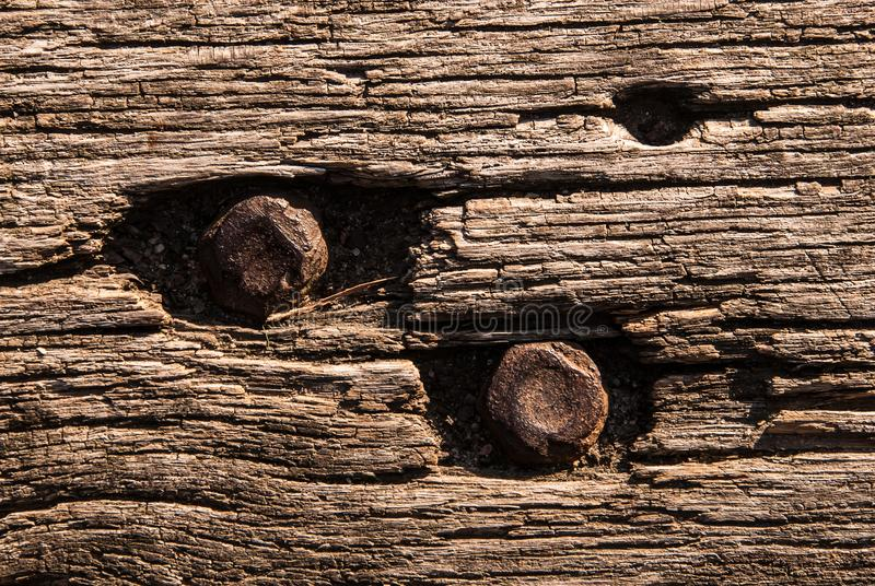 Grunge Faded Wood Board Panel Structure With Metal Screws. Old wooden bench texture, closeup. Aged Solid Wood Slat Rustic Shabby Brown Background With Rusty Nut stock photo