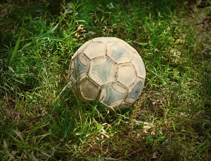 Grunge football or soccer ball on a green lawn royalty free stock images