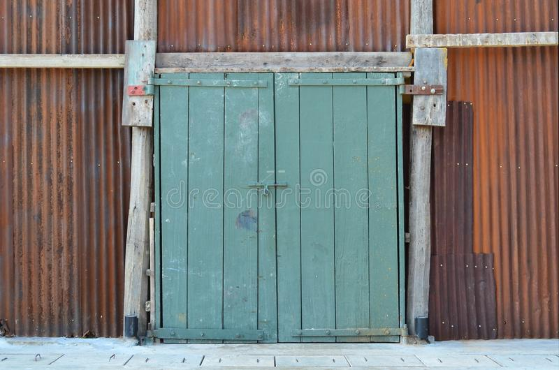 Grunge green wooden door with padlock on rusted metal galvanized stock photo