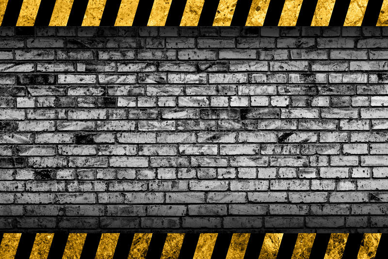 Grunge grey brick wall background with warning stripes stock illustration