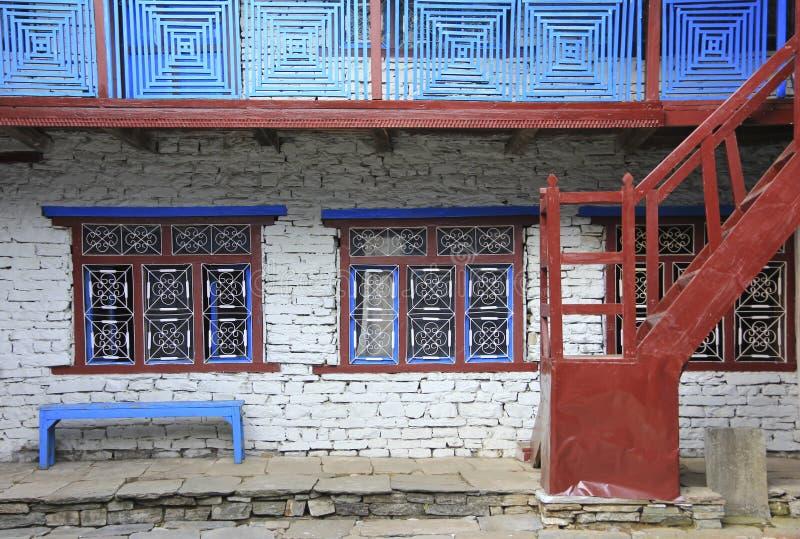 Grunge grijze bakstenen muur met rode vensters en wit gebogen staal, stock foto