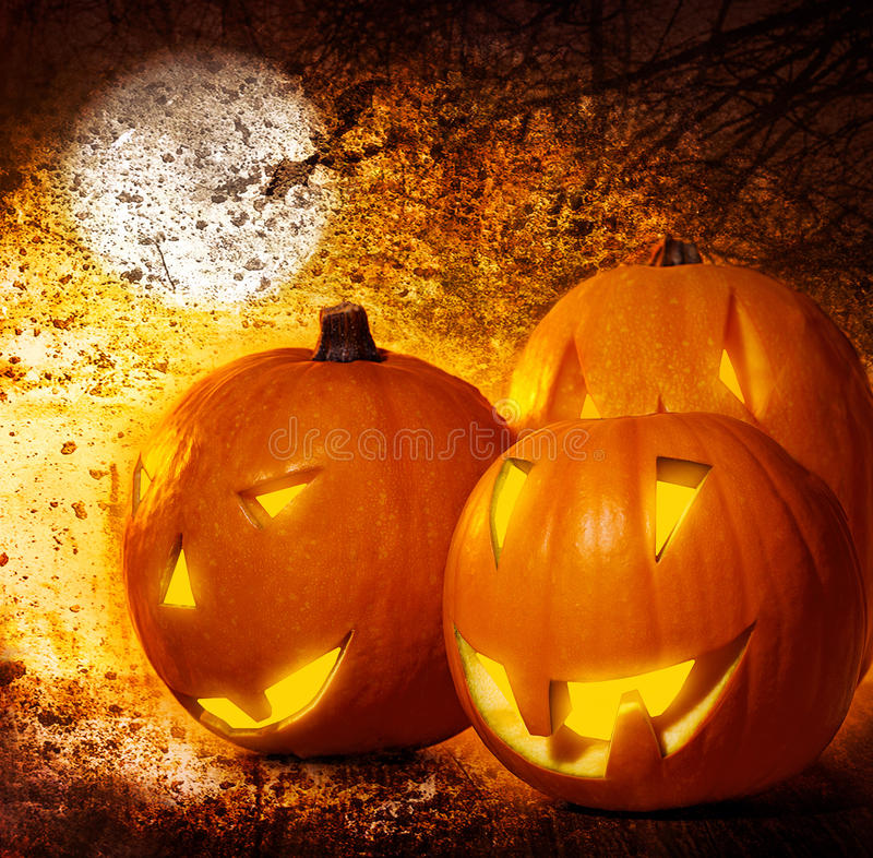 Grunge Halloween background. Pumpkins on the cemetery at night, scary spooky decoration, autumn holiday royalty free stock image
