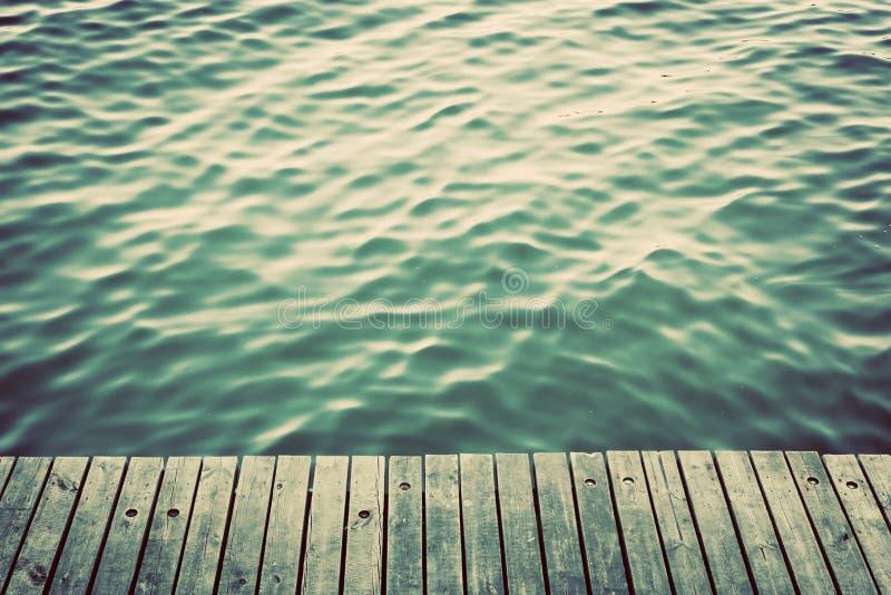 Grunge houten raad van een pijler over oceaan met golvende golven wijnoogst stock foto's