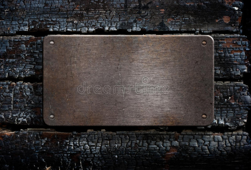Grunge Metal Plate Over Burned Wooden Background Royalty Free Stock Images