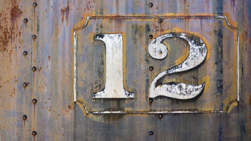 Grunge metal twelve. Grunge rusty metal background with faded paint number twelve stock photos