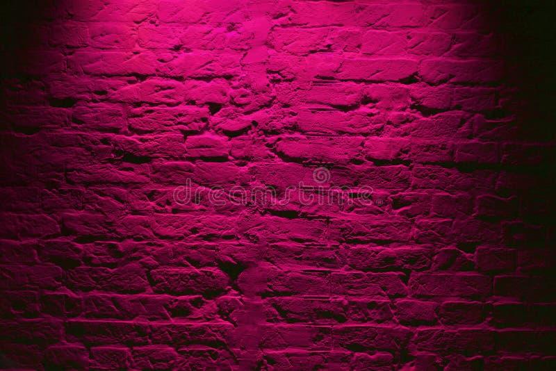 Grunge neon pink brick wall texture background. Magenta colored brick wall texture architecture pattern stock image