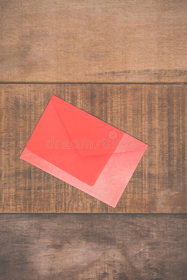 Grunge red envelope on wooden background stock photography