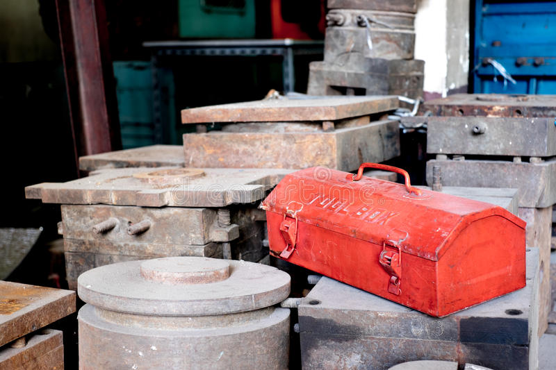 Grunge red metal tool box on rustic moles in factory.  royalty free stock image
