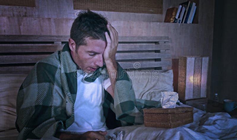 Grunge redigerar på trött och slösat sjukt hemmastatt frysa för man i säng som täckas med grippe för filtlidandehuvudvärken som k royaltyfria foton