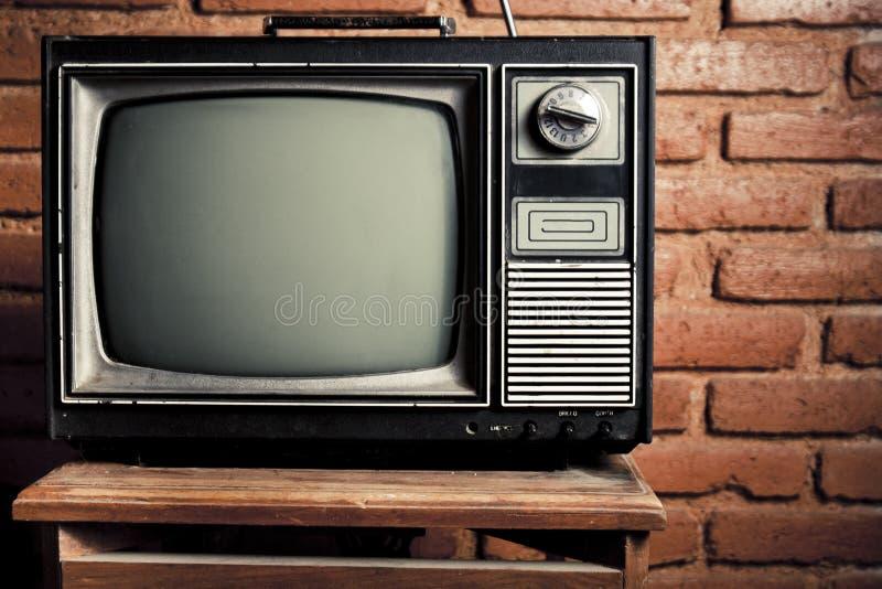 Grunge retro TV contra la pared de ladrillo. fotos de archivo libres de regalías
