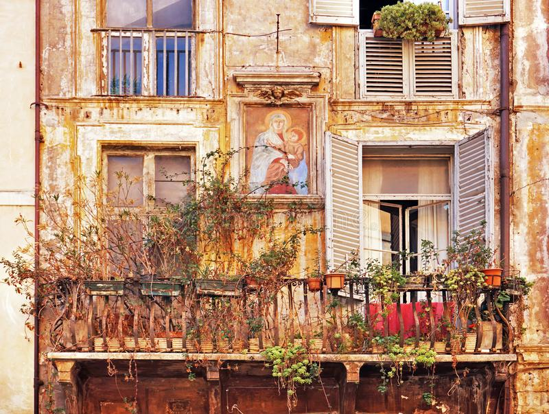Grunge shabby wall of an ancient italian house with a balcony and windows with shutters and potted plants and an icon of Our stock image