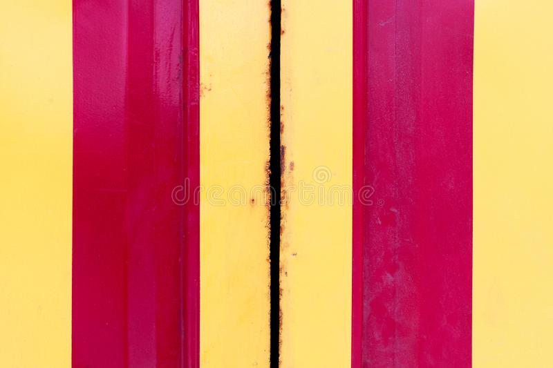 Grunge steel doors with yellow and red vertical stripes. metal corrosion at metal borders. texture pattern for design. part of gas royalty free stock images