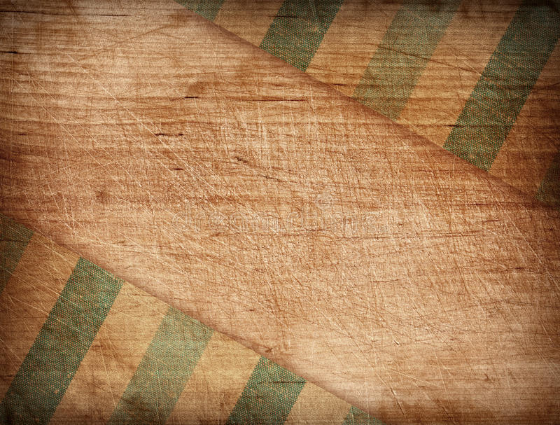 Grunge striped tablecloth on wooden cutting board royalty free stock photography