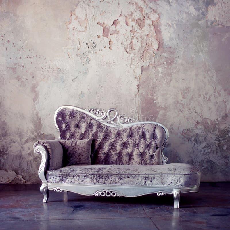 Grunge utformad inre Härlig soffa i klassisk stil på en bakgrund av texturerade väggar Purpurfärgad toning royaltyfri foto