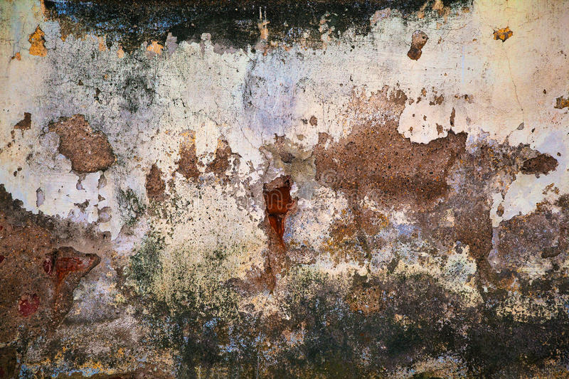 Grunge wall texture background. Paint cracking off dark wall with rust underneath stock images