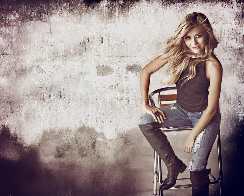Grunge wall and woman. Beautiful blond woman in ripped jeans and hair blowing in the wind sitting against grunge wall with space for text stock images