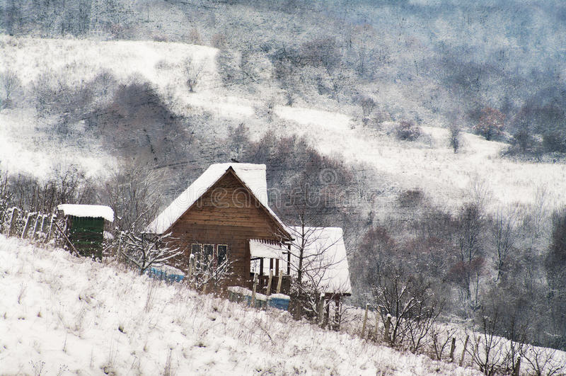Grunge winter landscape. Grunge, painterly winter landscape with a small house in the mountains stock photo