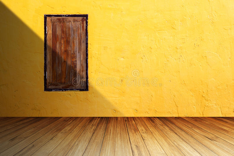Grunge wood window on bright orange concrete wall against perspective wood floor with shadow from left side. royalty free stock images