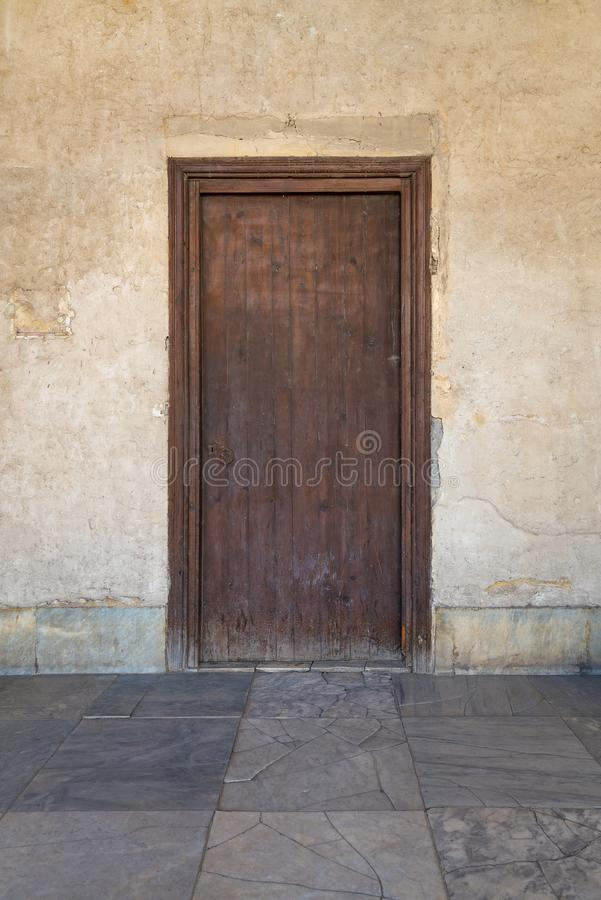 Grunge wooden aged door on weathered stone wall stock photography