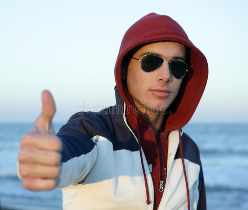 Grunge young man with hood at the beach stock photos