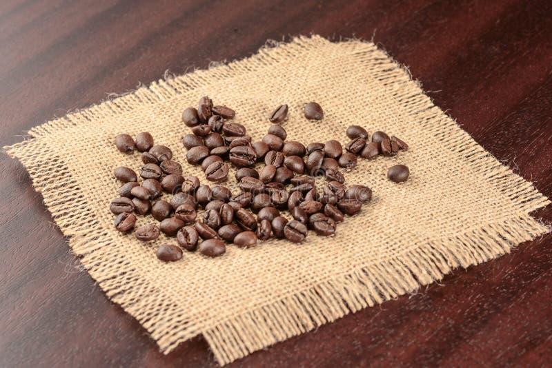 Grungebakgrund med stället för text Grillade kaffebönor på den verkliga jutesäckvävservetten som ligger på den bruna tabellen arkivfoton