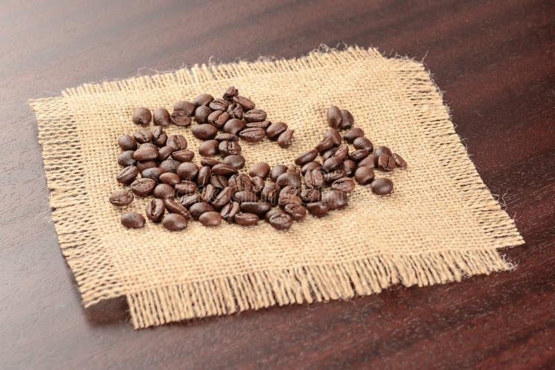 Grungebakgrund med stället för text Grillade kaffebönor på verklig jutesäckvävservett royaltyfri fotografi
