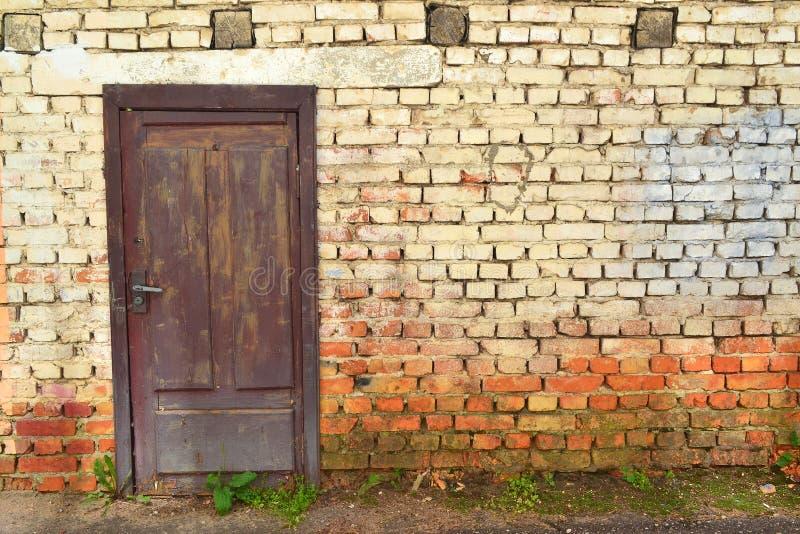 Grungebakstenen muur, oud metselwerk die, A oude bakstenen muur van een de 18de eeuwfort verslechteren met houten deur Retro uits stock foto