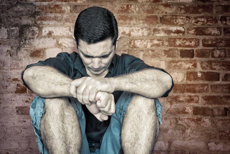 Grungebeeld van een gedeprimeerde en eenzame jonge mens stock foto