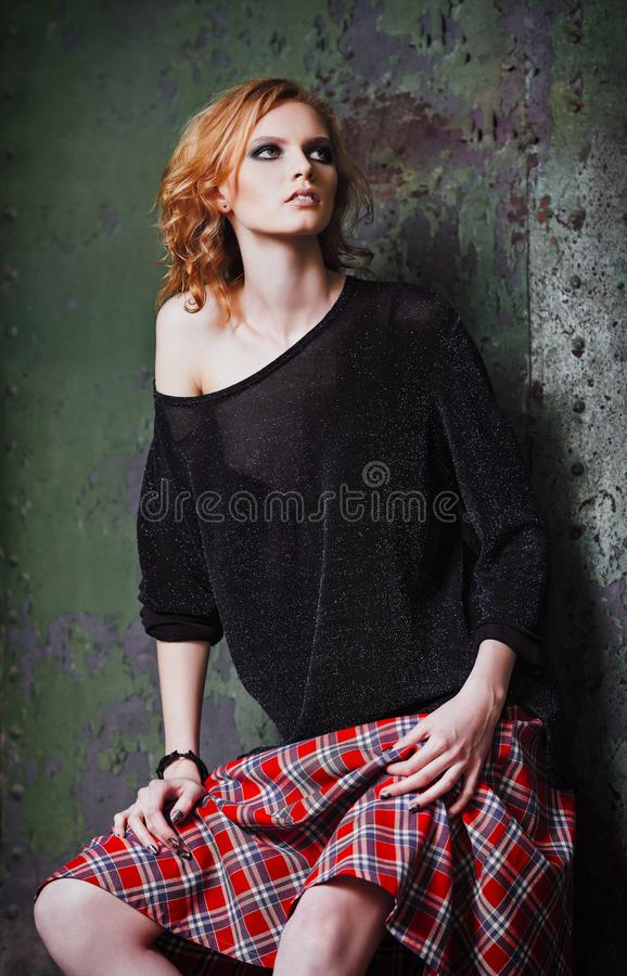 Grungemanier: portret van het mooie jonge informele model van het roodharigemeisje in plaidrok en blouse stock fotografie