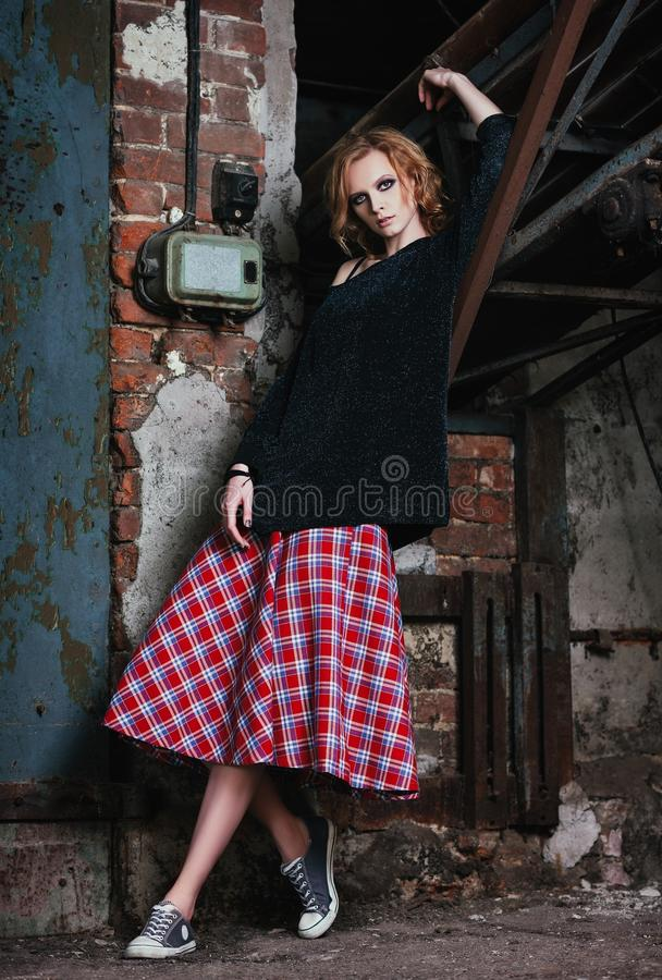 Grungemanier: portret van mooie jonge vrouw in geruit rok en jasje stock foto