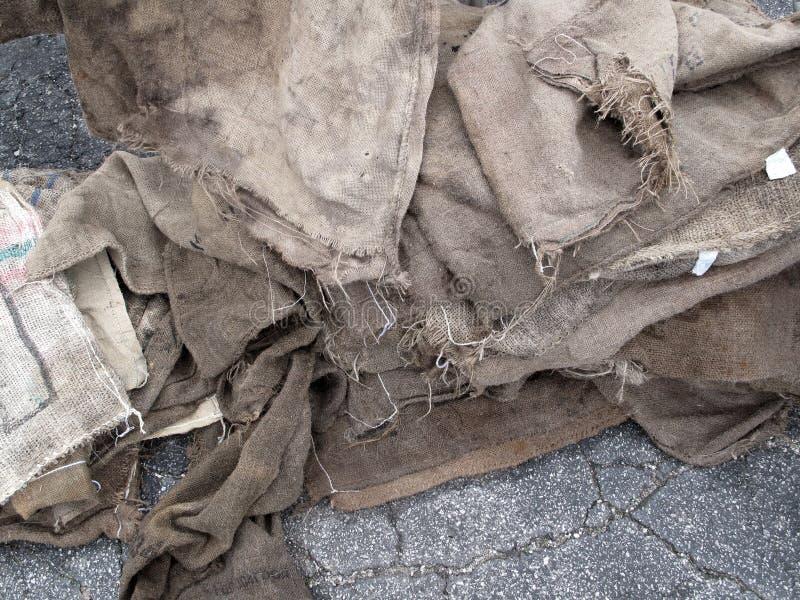 Grungesäckvävsäckar på asfalt arkivfoton