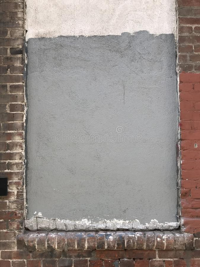 Grungy brick wall with frame and cement stock image
