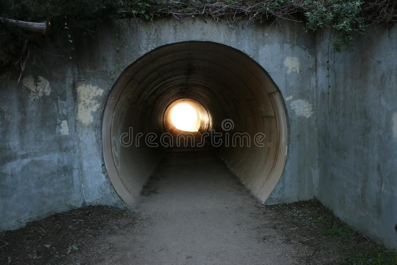 Long, empty tunnel with light at the end. Grungy cement walls frame the entrance to a empty tunnel. A tunnel is a metaphor for many things stock photography