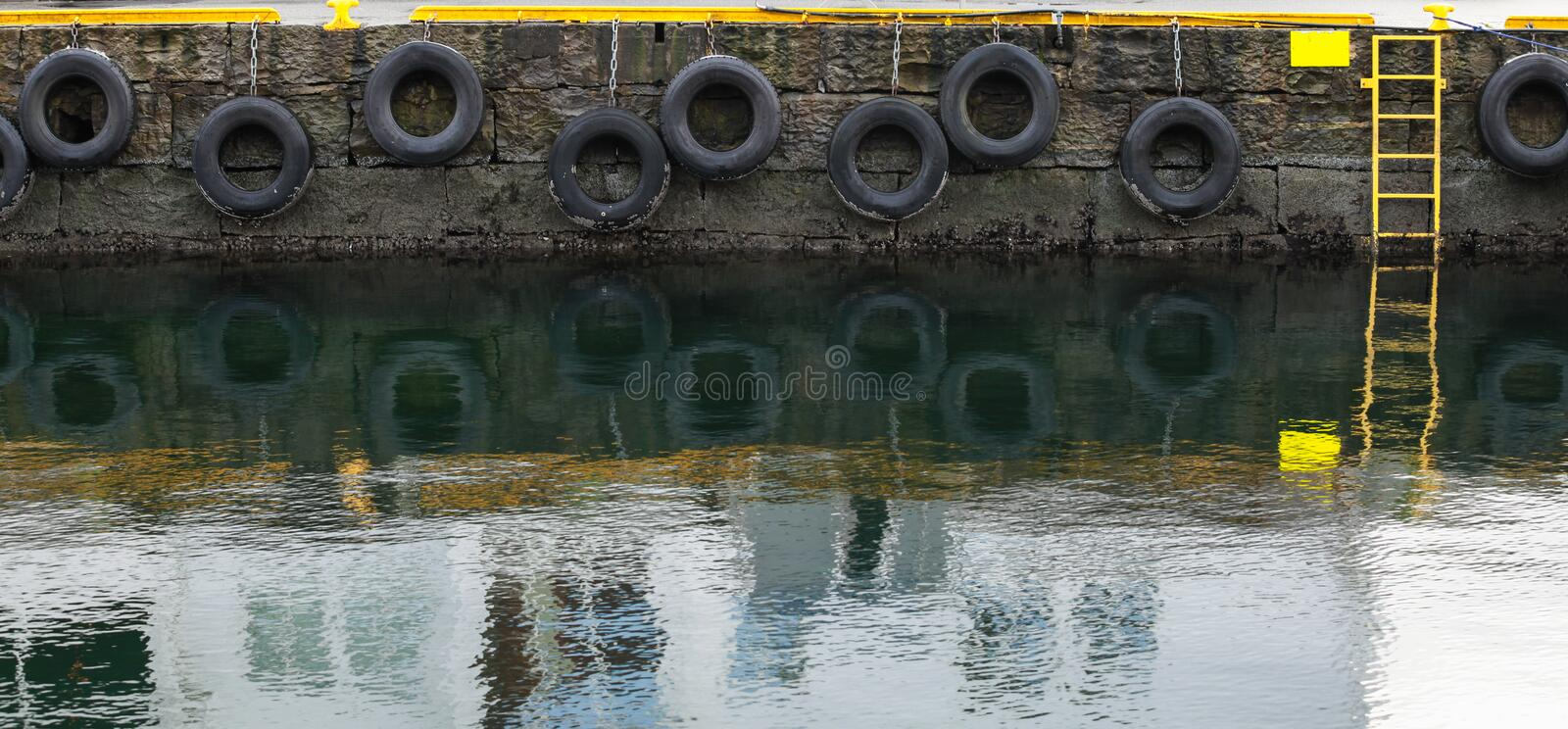 Grungy concrete mooring wall with hanging tires. As bumpers, background photo texture royalty free stock photos