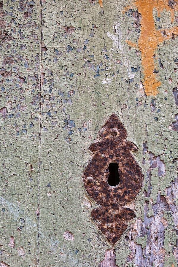Grungy dörr med sprucken målarfärg och den rostiga nyckelhålet arkivbild