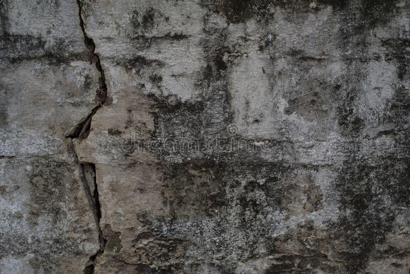 Grungy grey cracked brick wall. Texture royalty free stock photo