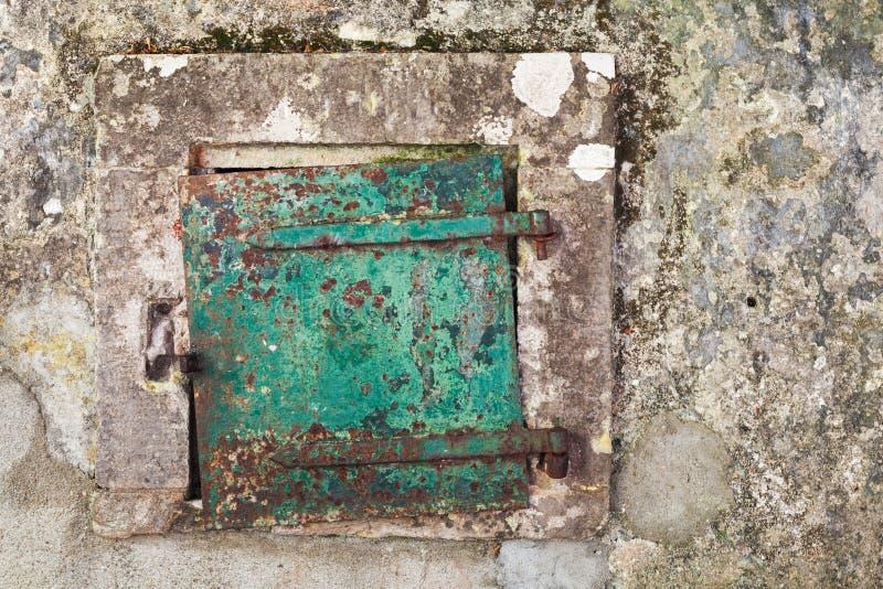 Grungy groene metaaldeur in grijze concrete muur stock afbeelding
