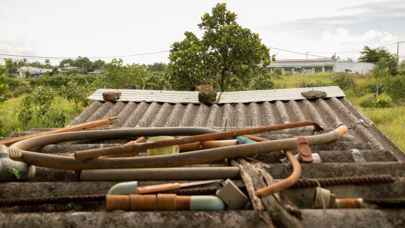 Grungy korrugerat tak för tappning med övergav ventiler för slang för vattenrör lantliga plast- och Rusty Metal Junk - bygdträdgå royaltyfria foton