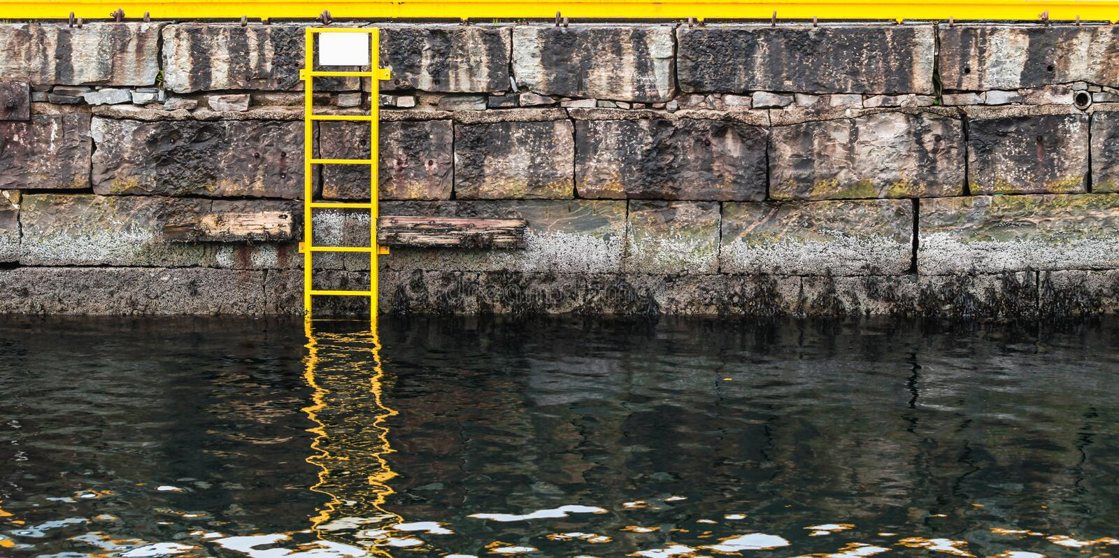 Grungy mooring wall and sea water, stone pier. With yellow ladder, background photo stock image