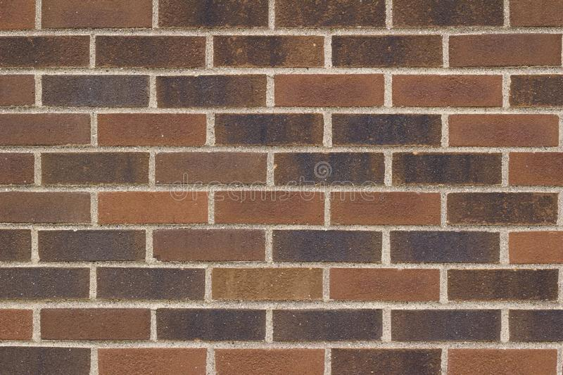 Grungy multi-hued brown brick wall texture in a traditional running bond pattern royalty free stock images