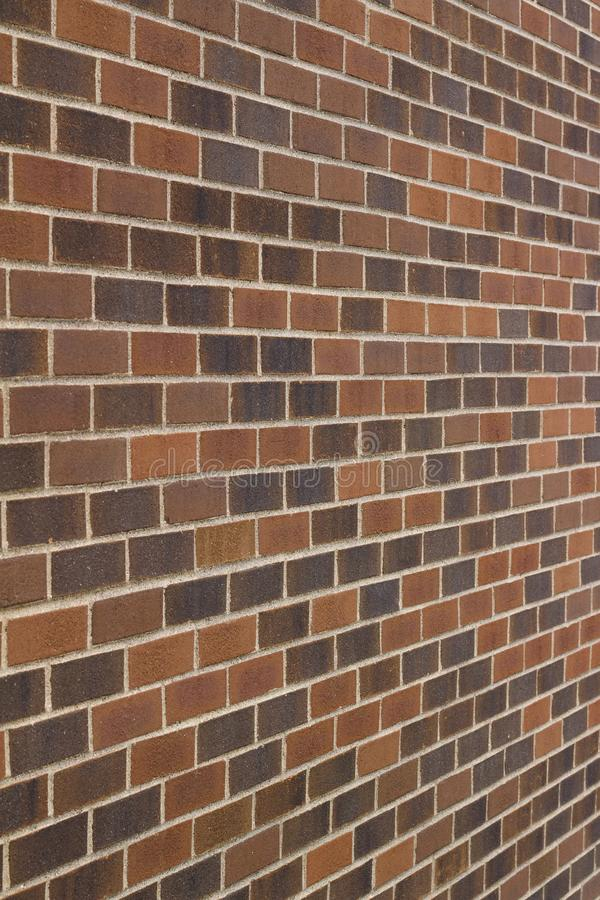 Grungy multi-hued brown brick wall texture in a traditional running bond pattern royalty free stock photography