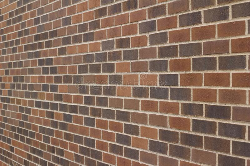 Grungy multi-hued brown brick wall texture in a traditional running bond pattern royalty free stock image